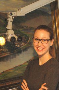 Restauratorin Farina Bebenek vor einem Gemälde mit Auflichtmikroskop Zeiss OPMI 99